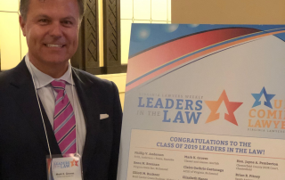 Image of Mark Groves in beside Leaders in the Law poster