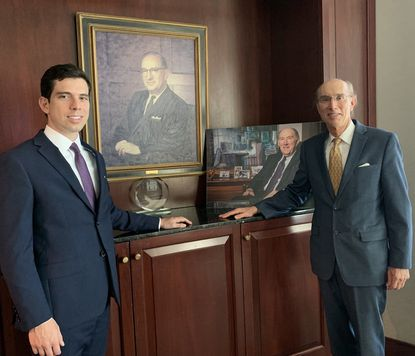 Image of Jake and Michael Glasser in front of Bernard and Richard Glassers' portrait